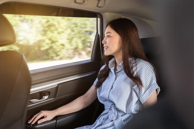 Młoda kobieta myśli i wygląda przez okno, siedząc na tylnym siedzeniu samochodu