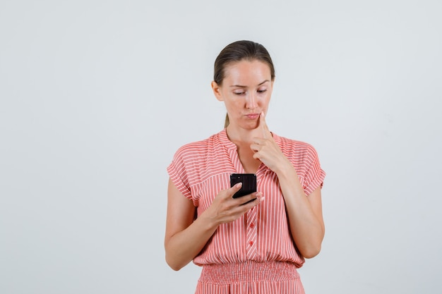 Młoda kobieta myśli patrząc na telefon komórkowy w pasiastej sukni widok z przodu.