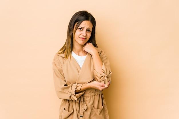 Młoda kobieta na beżowej ścianie masuje łokieć, cierpi po złym ruchu