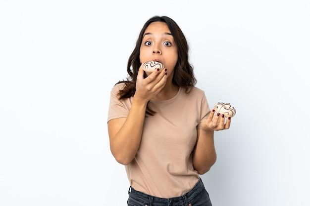 Młoda kobieta na białym tle białe tło trzyma pączek