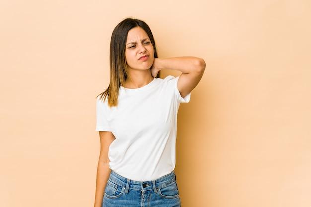 Młoda kobieta na białym tle na beżowy cierpi na ból szyi z powodu siedzącego trybu życia.