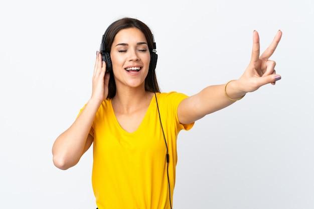 Młoda kobieta na białym tle na białej ścianie słuchania muzyki i śpiewu