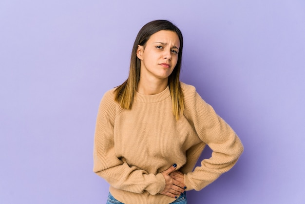 Młoda kobieta na białym tle na fioletowej ścianie o ból wątroby, ból brzucha.