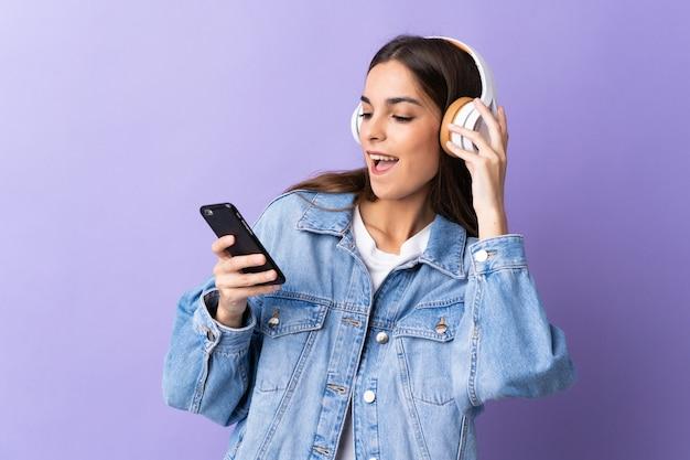 Młoda kobieta na białym tle na fioletowej ścianie słuchania muzyki z telefonu komórkowego i śpiewu