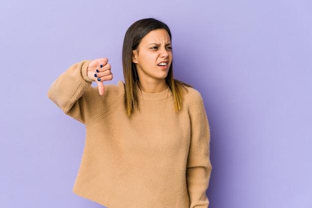 Młoda kobieta na białym tle na fioletowym tle, pokazując kciuk w dół i wyrażając niechęć.