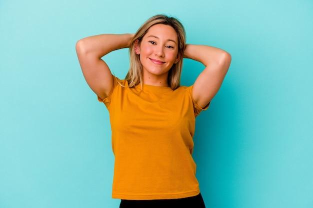 Młoda kobieta na białym tle na niebieskiej ścianie czuje się pewnie, z rękami za głową