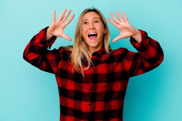 Młoda kobieta na białym tle na niebieskiej ścianie krzycząc podekscytowany do przodu