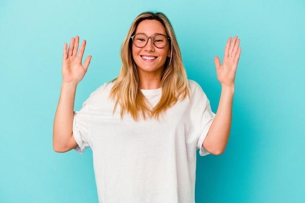 Młoda kobieta na białym tle na niebieskiej ścianie radosny śmiech dużo
