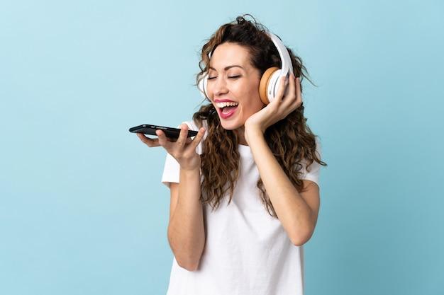 Młoda kobieta na białym tle na niebieskiej ścianie słuchanie muzyki z telefonu komórkowego i śpiewu