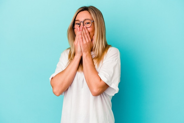 Młoda kobieta na białym tle na niebieskiej ścianie śmiejąc się z czegoś, obejmując usta rękami