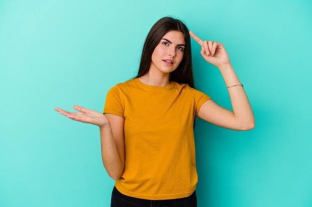 Młoda kobieta na białym tle na niebieskiej ścianie, trzymając i pokazując produkt pod ręką