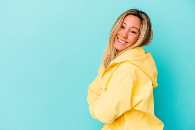 Młoda kobieta na białym tle na niebieskiej ścianie uśmiechnięty pewnie ze skrzyżowanymi rękami