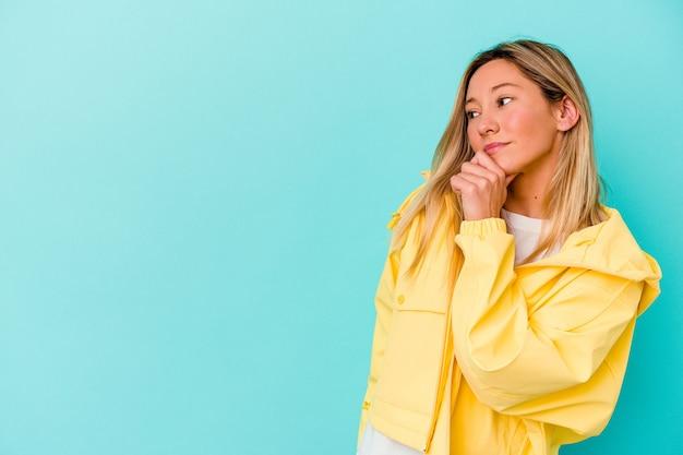 Młoda kobieta na białym tle na niebieskiej ścianie zrelaksowany, myśląc o czymś patrząc na przestrzeń kopii