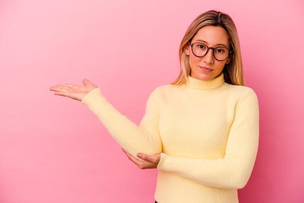 Młoda kobieta na białym tle na różowej ścianie pokazując miejsce na kopię na dłoni i trzymając drugą rękę na talii