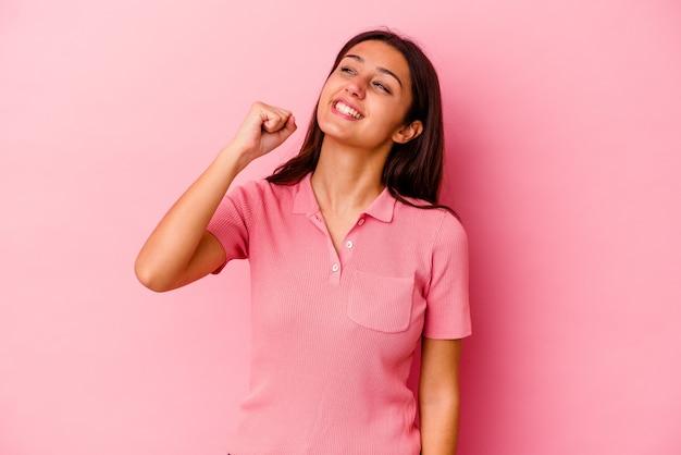 Młoda kobieta na białym tle na różowej ścianie świętuje zwycięstwo, pasję i entuzjazm, szczęśliwy wyraz