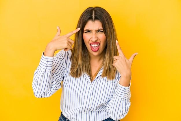 Młoda kobieta na białym tle na żółtej ścianie pokazuje gest rozczarowania palcem wskazującym