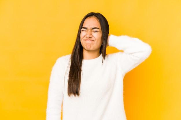 Młoda kobieta na białym tle na żółtym miejscu cierpi na ból szyi z powodu siedzącego trybu życia.