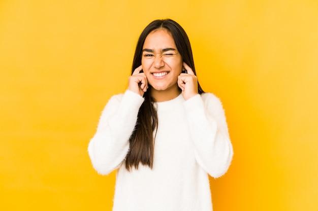 Młoda kobieta na białym tle na żółtym tle obejmujące uszy rękami.
