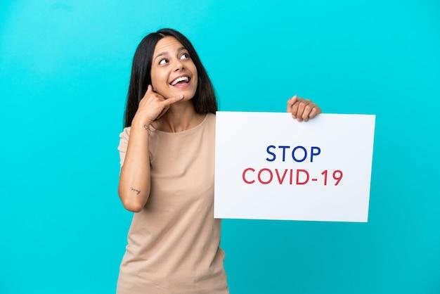 Młoda kobieta na białym tle trzyma afisz z tekstem stop covid 19 i robi gest telefoniczny