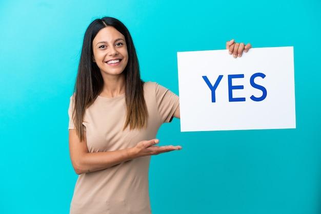 Młoda kobieta na białym tle trzyma afisz z tekstem tak ze szczęśliwym wyrazem twarzy