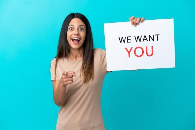 Młoda kobieta na białym tle trzyma deskę we want you i wskazuje na przód