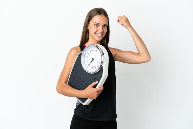 Młoda kobieta na białym tle trzyma maszynę do ważenia i robi silny gest