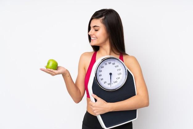 Młoda kobieta na białym tle trzyma maszynę do ważenia, patrząc na jabłko