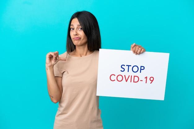 Młoda kobieta na białym tle trzyma plakat z tekstem stop covid 19 z dumnym gestem