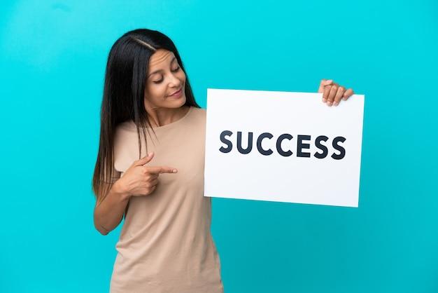 Młoda kobieta na białym tle trzyma plakat z tekstem sukces i wskazuje go