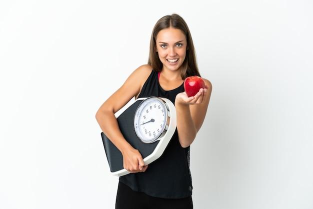 Młoda kobieta na białym tle trzymająca wagę i oferująca jabłko