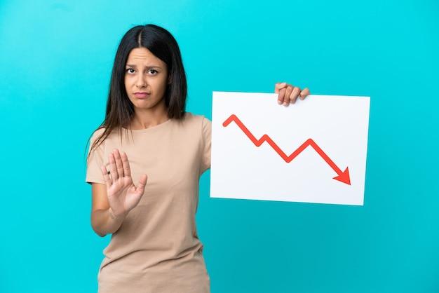Młoda kobieta na białym tle trzymająca znak z malejącym symbolem strzałki statystyk i robiąca znak stop
