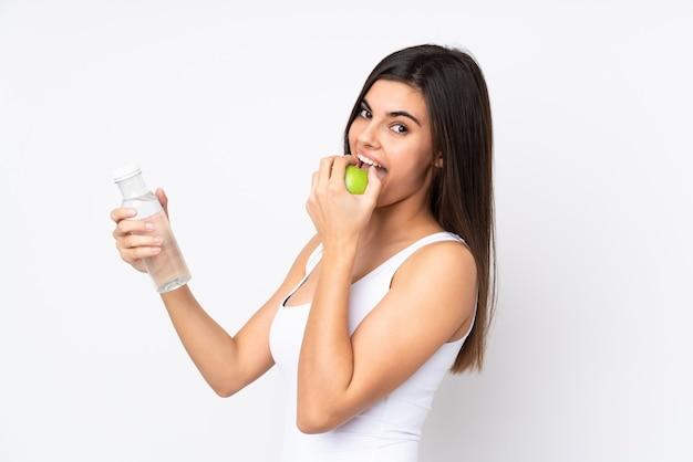 Młoda kobieta na białym tle z jabłkiem i butelką wody
