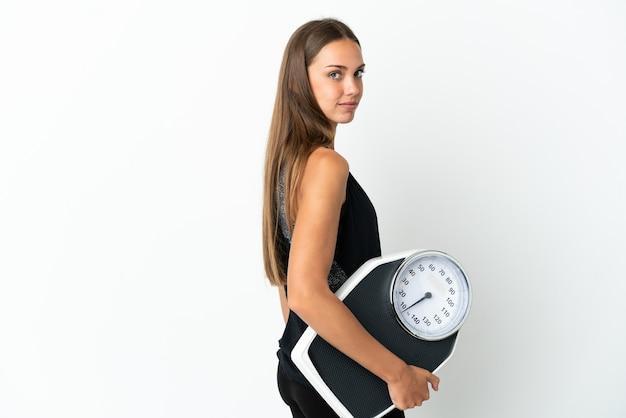 Młoda kobieta na białym tle z maszyną do ważenia