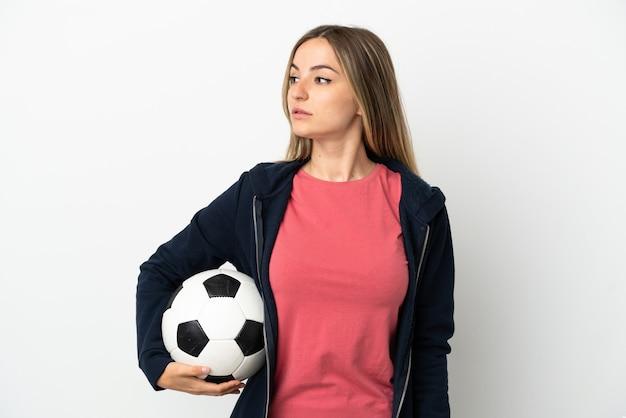 Młoda kobieta na białym tle z piłką nożną