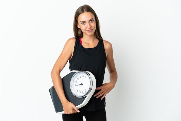 Młoda kobieta na białym tle z rękami na biodrze i trzymając wagę