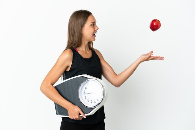 Młoda kobieta na białym tle z wagą i jabłkiem