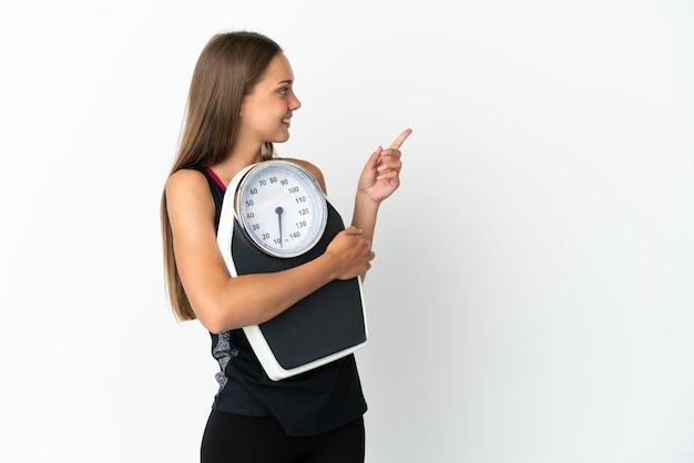 Młoda kobieta na białym tle z wagą i wskazującą stroną