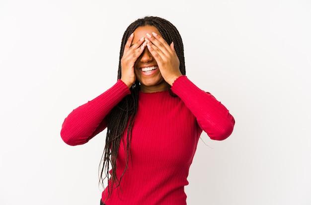 Młoda kobieta na białym tle zakrywa oczy dłońmi, uśmiecha się szeroko, czekając na niespodziankę