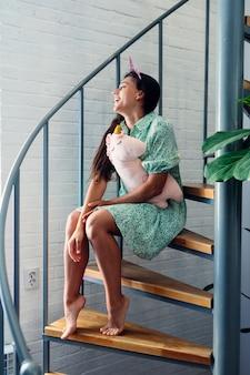 Młoda kobieta na drewnianych schodach w nowoczesnym domu.