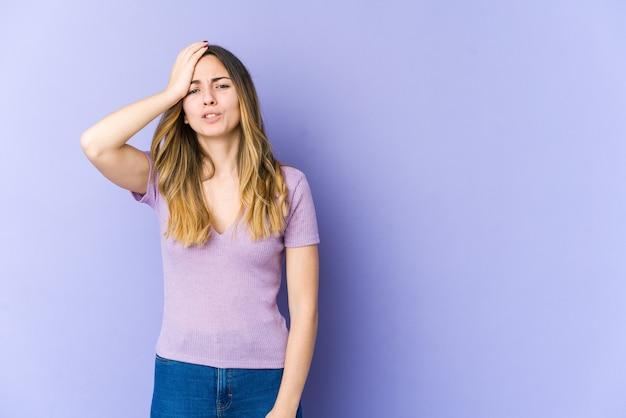 Młoda kobieta na fioletowej ścianie zapominając o czymś, uderzając dłonią w czoło i zamykając oczy