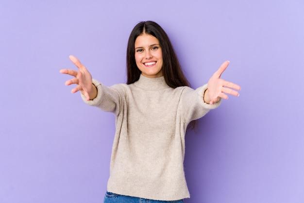 Młoda kobieta na fioletowo czuje się pewnie, ściskając aparat.