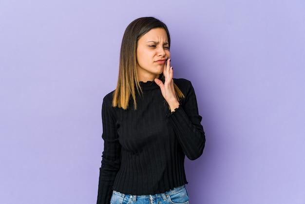 Młoda kobieta na fioletowym tle o silnym bólu zębów, bólu trzonowego.