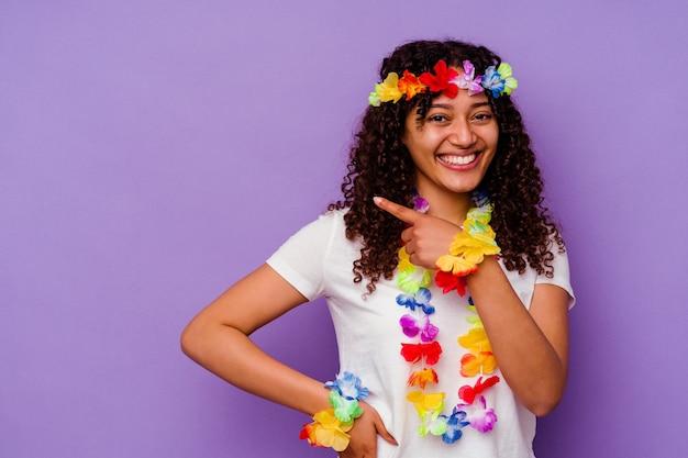 Młoda kobieta na hawajach na białym tle na fioletowym tle, uśmiechając się i wskazując na bok, pokazując coś w pustym miejscu.