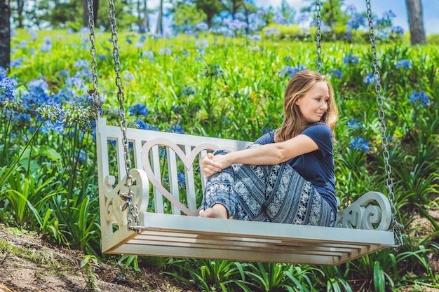 Młoda kobieta na huśtawce w ogrodzie kwiatowym