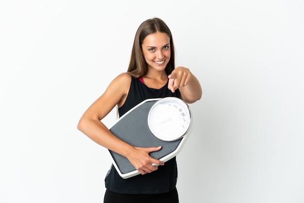 Młoda kobieta na izolowanych białej ścianie trzyma maszynę do ważenia i wskazując do przodu