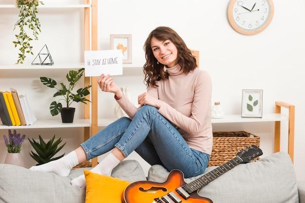 Młoda kobieta na kanapie z gitarą