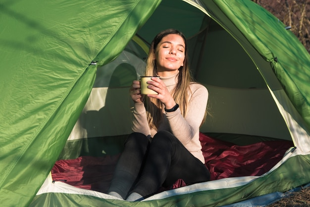 Młoda kobieta na kempingu w zachód słońca, siedząc w namiocie i picia kawy ze stalowego kubka