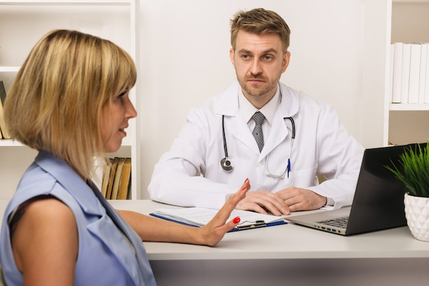 Młoda kobieta na konsultacji z chirurgiem lub terapeutą w swoim gabinecie. selektywne skupienie się na lekarzu.