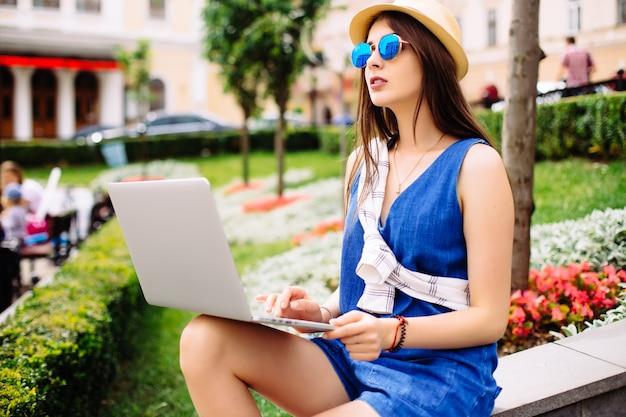 Młoda kobieta na ławce z laptopem na zewnątrz
