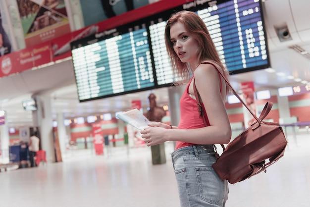 Młoda kobieta na lotnisku z mapą w rękach i tablicą informacyjną z tyłu patrzy w bok